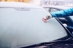 Woman removing ice from car windshield with glass scraper. Frosty morning Royalty Free Stock Image