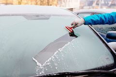 Woman removing ice from car windshield with glass scraper. Royalty Free Stock Photography