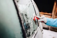 Woman removing ice from side car windshield. With glass scraper. Frosty morning Royalty Free Stock Images