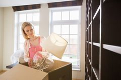 Woman removing lamp from cardboard box at new home royalty free stock photos