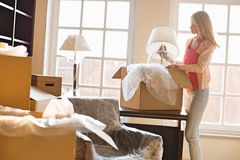 Woman removing lamp from moving box at new house royalty free stock photos
