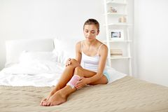 Woman removing leg hair with depilatory wax strip Royalty Free Stock Photo