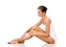 Woman removing leg hair with depilatory wax strip Royalty Free Stock Photos