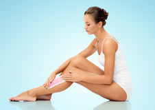Woman removing leg hair with depilatory wax strip Royalty Free Stock Photos