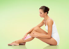Woman removing leg hair with depilatory wax strip Stock Photography