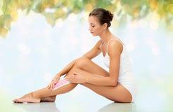 Woman removing leg hair with depilatory wax strip Royalty Free Stock Image
