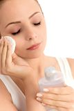 Woman removing make-up. Young woman using cotton pad on face, portrait royalty free stock photography