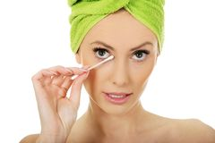 Woman removing make up with cotton bud. Stock Photography