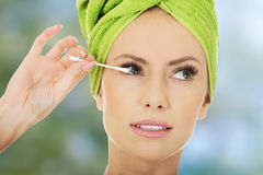 Woman removing make up with cotton bud. Stock Images