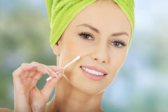 Woman removing make up with cotton bud. Royalty Free Stock Image