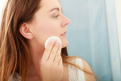 Woman removing makeup with cotton swab pad. Royalty Free Stock Image