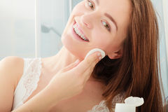 Woman removing makeup with cotton swab pad. Royalty Free Stock Photo