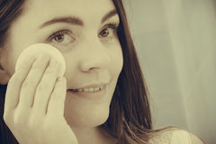 Woman removing makeup with cotton swab pad. Royalty Free Stock Photos