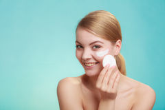 Woman removing makeup with cream and cotton pad Stock Photo