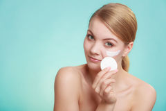 Woman removing makeup with cream and cotton pad Royalty Free Stock Image
