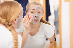 Woman removing mud facial mask with sponge Royalty Free Stock Photo