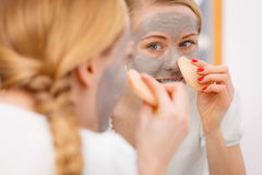 Woman removing mud facial mask with sponge Royalty Free Stock Images