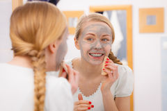 Woman removing mud facial mask with sponge Stock Photos