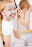 Woman removing mud facial mask with sponge Royalty Free Stock Image