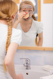 Woman removing mud facial mask with sponge Royalty Free Stock Photography