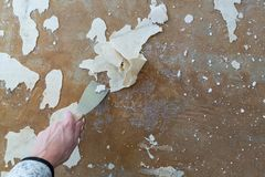 Woman is removing the old carpet residue from the floor royalty free stock photos