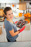 Woman removing from oven tray with homemade Halloween cookies Stock Image