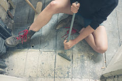 Woman removing paint from floorboards Stock Photo