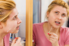 Woman removing peel off mask from her face Stock Photography