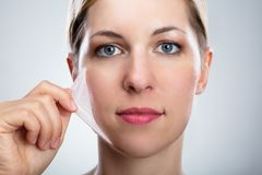 Free Woman Removing Peeling Mask From Her Face Royalty Free Stock Photos - 149004098