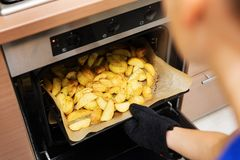 Woman removing prepared potatoes tray out of oven Royalty Free Stock Image