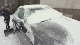 Woman removing snow around the car in snowfall. In winter day stock video