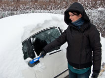 Woman removing snow from car Stock Photos