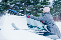 Woman Removing Snow from a Car with a Broom Stock Photo