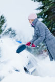 Woman Removing Snow from a Car with a Broom Royalty Free Stock Photography