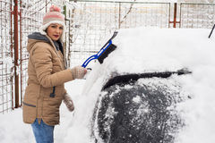 Woman removing snow from car Royalty Free Stock Photo
