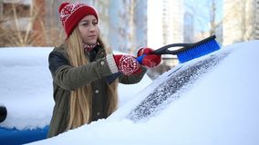 Woman removing snow from car windshield stock video footage