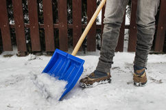 Woman removing snow from the sidewalk Stock Photo