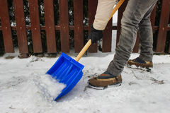 Woman removing snow from the sidewalk Stock Image
