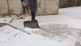 Woman removing snow in yard. In winter day stock video footage