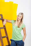 Woman renovating her house. Leaning against a wooden ladder with a satisfied smile as she surveys the new yellow paint on the wall Royalty Free Stock Image
