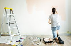Woman renovating the house wall painting Stock Image