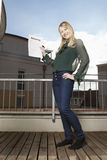Woman with rental agreement. Young woman on the balcony proudly showing her tenancy agreement Royalty Free Stock Photography