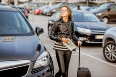 Woman renting a car. Portrait of a young happy woman standing with rental contract and suitcase outdoors on the car parking Stock Photos