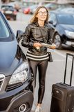Woman renting a car. Portrait of a young happy woman standing with rental contract and suitcase outdoors on the car parking Stock Images