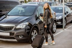 Woman renting a car. Portrait of a young and happy woman traveling with suitcase near the rental car outdoors on the parking Stock Photo