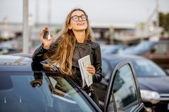 Woman renting a car. Portrait of a young woman showing keys near the rental car on the parking Stock Photography
