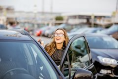 Woman renting a car. Portrait of a young woman standing with rental contract outdoors on the car parking near the airport Royalty Free Stock Images