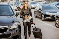 Woman renting a car. Young and happy woman walking with suitcase holding rental contract on the car parking Royalty Free Stock Image
