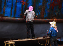 Woman repair old ship. In Xiapu,fujian province of China, there loacated a small old ship repair factory, this picture showed 2 woman remove the rust of the iron Royalty Free Stock Image