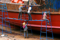 Woman repair old ship. In Xiapu,fujian province of China, there loacated a small old ship repair factory, this picture showed 2 woman remove the rust of the iron Stock Images